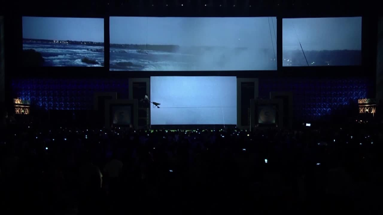 20,000 Entrepreneurs, Celebrities and Friends witness President & CEO of Market America | SHOP.COM, JR Ridinger, launch The Shopping Annuity while walking a high wire over Niagara Falls while pushing a wheelbarrow full of bricks proving that anything is possible with belief.